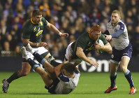 South Africa's Steven Kitshoff, second right, is tackled by Scotland's Huw Jones, bottom, during the rugby union international match between Scotland and South Africa at Murrayfield stadium, in Edinburgh, Scotland, Saturday, Nov. 17, 2018. (AP Photo/Scott Heppell)