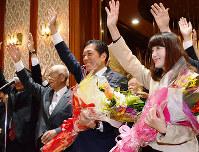 愛媛県知事選で当選が確実になり、花束を抱えながら万歳する中村時広氏(中央)ら=松山市大街道3のいよてつ会館で、木島諒子撮影