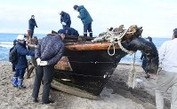 Police officers check inside a wooden boat on Nov. 13, 2018 that was washed ashore in the northwestern Japan city of Akita. (Mainichi/Shun Kawaguchi)