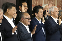 From left, Chinese President Xi Jinping, Papua New Guinea's Prime Minister Peter O'Neill, Japanese Prime Minister Shinzo Abe, and U.S. Vice President Mike Pence wave as they pose for a group photo at APEC Haus in Port Moresby, Papua New Guinea, Sunday, Nov. 18, 2018. (AP Photo/Mark Schiefelbein)