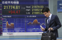 A man walks by an electronic stock board of a securities firm in Tokyo, Monday, Nov. 19, 2018. (AP Photo/Koji Sasahara)