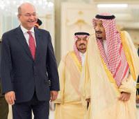 In this photo provided by the Saudi Press Agency, Saudi King Salman, right, walks with with Iraqi President Barham Salih, in Riyadh, Saudi Arabia, on Nov. 18, 2018. (AP Photo/Saudi Press Agency)