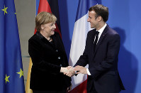German Chancellor Angela Merkel, left, and France's President Emmanuel Macron, right, shake hands after a joint statement prior to a meeting at the chancellery in Berlin, Germany, on Nov. 18, 2018. (AP Photo/Michael Sohn)