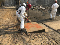 A volunteer member of an El Dorado County search and rescue team uses orange spray paint to mark the ruins of a home to show that no human remains were found at the location in Paradise, Calif., on Nov. 18, 2018, following a Northern California wildfire. (AP Photo/Sudhin Thanawala)