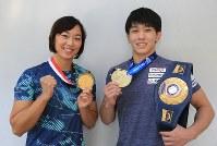 アジア大会の競泳とレスリングの世界選手権で獲得した金メダルやベルトを手に笑顔を見せる鈴木聡美(左)と乙黒拓斗=内林克行撮影