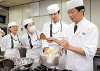 An instructor, far right, shows how to cook a Japanese dish as Vaelinoro van Ann Varvara, far left, and other students look on, at Tsuji Culinary Institute in Osaka's Abeno Ward in western Japan, on Oct. 16, 2018. (Mainichi/Kentaro Ikushima)