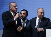 Turkey's President Recep Tayyip Erdogan, left, and Russian President Vladimir Putin, right, hold hands as they attend an event marking the completion of one of the phases of the Turkish Stream natural gas pipeline, in Istanbul, on Nov. 19, 2018. (AP Photo/Lefteris Pitarakis)