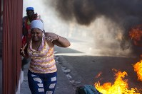 Residents run past burning barricades during a strike that is part of protests demanding to know how Petro Caribe funds have been used by the current and past administrations, in Port-au-Prince, Haiti, on Nov. 19, 2018. (AP Photo/Dieu Nalio Chery)