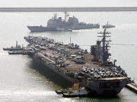 In this March 22, 2007, file photo, the U.S. aircraft carrier USS Ronald Reagan, bottom, anchors as U.S. Aegis Ship passes after they arrive at Busan port for joint military exercises in Busan, South Korea. (AP Photo/ Lee Jin-man)