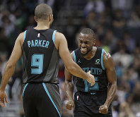 Charlotte Hornets' Kemba Walker (15) celebrates with Tony Parker (9) after Parker's basket against the Boston Celtics late in the second half of an NBA basketball game in Charlotte, North Carolina, on Nov. 19, 2018. (AP Photo/Chuck Burton)