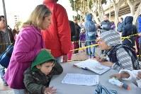 難民申請の順番を待つ登録名簿に氏名や国籍を記入してもらう家族=メキシコ北西部ティフアナで19日