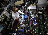 データ復旧のため、顕微鏡をのぞきながらパソコンの記憶装置の基板を修理する下垣内太さん=大阪市北区で2018年10月20日、小松雄介撮影