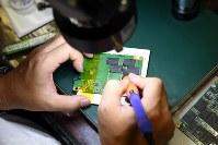 はんだごてを操りパソコンの記憶装置の基板を修理。データ復旧の手順の多くは手作業だ=大阪市北区で2018年10月20日、小松雄介撮影