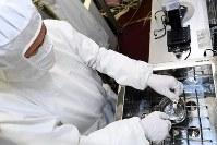 空気清浄装置を備えたクリーンルームで記憶装置の部品を清掃する下垣内太さん=大阪市北区で2018年10月20日、小松雄介撮影