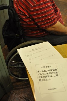 A man in a wheelchair recalls how sad and angry he felt when he was handed a paper urging wheelchair users to refrain from tasting wine at a department store in Tokyo. Shown in the foreground is a copy of the paper in question. (Mainichi/Yuka Narita)