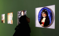A woman admires creations by British artist Banksy during a press preview of the