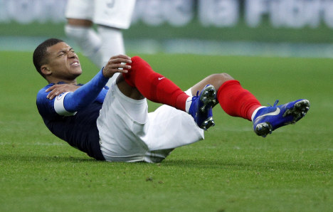 France's Kylian Mbappe grimaces in pain after being tackled by Uruguay goalkeeper Martin Campana during the international friendly soccer match between France and Uruguay at the Stade de France stadium in Saint-Denis, outside Paris, on Nov. 20, 2018. (AP Photo/Francois Mori)