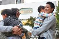 息子を抱きかかえ友人と笑うXジェンダーの丸山真由(まさよし)さん(34、右)=東京都武蔵野市で2018年10月25日、渡部直樹撮影