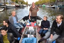 アムステルダムの運河でごみ釣りツアーに参加する人たち。船尾に立つのはガイドのデ・ボートさん=アムステルダムで2018年11月6日、八田浩輔撮影