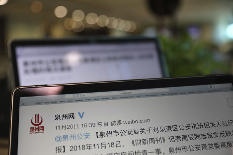 An online post by the Quanzhou police detailing the investigation and an apology for an incident where police personnel let themselves into the hotel room of Zhou Chen, an environmental reporter for Caixin, is seen on computer screens in Beijing, on Nov. 22, 2018. (AP Photo/Ng Han Guan)
