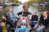 アムステルダムの運河でごみ釣りツアーに参加する人たち。船尾に立つのはガイドのデ・ボートさん=アムステルダムで2018年11月6日午後3時32分、八田浩輔撮影