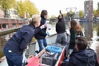 魚取り網や釣れたペットボトルを手にスマートフォンで記念撮影をするツアー参加者たち=アムステルダムで2018年11月6日午後3時23分、八田浩輔撮影