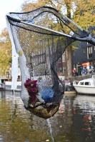 運河から魚取り網ですくい上げたペットボトル=アムステルダムで2018年11月6日午後4時36分、八田浩輔撮影