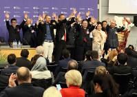 BIE総会のプレゼンテーションで壇上に上がって歌い、手を振る世耕弘成経産相ら日本の誘致関係者=パリのOECDカンファレンスセンターで2018年11月23日午後1時10分、幾島健太郎撮影