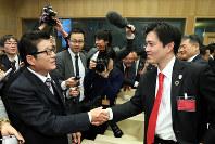 2025年万博の大阪開催が決まり、笑顔で握手する松井一郎・大阪府知事(左)と吉村洋文・大阪市長=パリのOECDカンファレンスセンターで2018年11月23日午後5時2分、幾島健太郎撮影