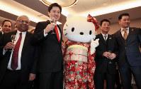 2025年万博の大阪開催が決まり、レセプションパーティーでキティちゃんと記念撮影する松井一郎・大阪府知事(右から2人目)と吉村洋文・大阪市長(同4人目)=パリで2018年11月23日午後7時40分、幾島健太郎撮影