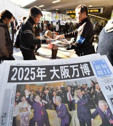 大阪万博決定の毎日新聞号外を受け取る人たち=大阪市北区で2018年11月24日午前8時53分、木葉健二撮影