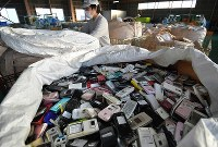 Used mobile phones are seen piled up at a recycle factory of an affiliated company of NTT Docomo Inc. in Ishikawa Prefecture on Nov. 8, 2018, before their precious metals will be collected for the production of medals for the 2020 Tokyo Olympics and Paralympics. (Mainichi/Koichiro Tezuka)