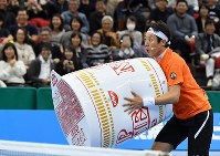 大きな「カップヌードル」を持ってプレーする松岡修造=名古屋市南区の日本ガイシホールで2018年11月25日、大西岳彦撮影