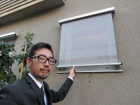 モデルハウスを案内する今泉太爾さん。屋外にあるブラインドは、夏の断熱に効果的という