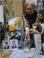 事故時に嘉久さんが身につけていた衣類を手にしながら、嘉久さんとの思い出を話す文子さん=静岡市清水区で2018年11月7日、木下翔太郎撮影