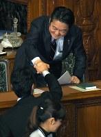 入管法改正案が衆院本会議で可決され、笑顔で握手を交わす山下貴司法相(上)=国会内で2018年11月27日午後9時45分、手塚耕一郎撮影
