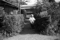 在日米軍飛行場の滑走路拡張を進める測量に反対する地元女性。「OFF LIMIT 立入禁止」の看板が掲げられた=東京都砂川町(現在の立川市砂川町)で1955年9月、東京本社写真部員撮影