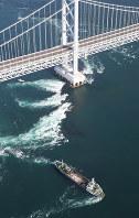 座礁した貨物船。奥は大鳴門橋=鳴門海峡で2018年11月30日午前9時49分、本社ヘリから小出洋平撮影