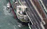 関西写真記者協会の協会賞を受賞した「台風21号 関空大打撃」(2枚組)から、関西国際空港の連絡橋に衝突したタンカー=2018年9月4日午後5時56分、本社ヘリから幾島健太郎撮影