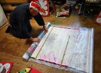 横の骨だけ残し、ビニールでカバーして丸めていく=千葉県長生村の凧工房ときで2018年11月15日、手塚耕一郎撮影