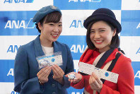 記念品を手にするANAの初代地上職制服(左)2代目地上職制服を着用したスタッフ=東京都大田区の羽田空港で2018年12月1日、米田堅持撮影