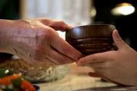 「できたよ、テーブルに運んでね」。週に一回夕食作りを担当する近隣住民の男性スタッフ(左)からスープを受け取るシェアハウスの子ども=東京都世田谷区で2018年10月、和田大典撮影