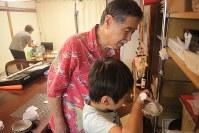 夕食作りや見守りを担当するシニアスタッフの男性とご飯をつぐ子ども=東京都世田谷区で2018年10月、和田大典撮影