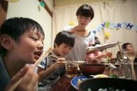 共有リビングで一緒に夕食をとる入居家族。平日の夕食づくりは山中さん(奥)やシニアスタッフらが日替わりで担う。親の帰りが遅くなっても子どもが一人で食事することはない=東京都世田谷区で2018年10月、和田大典撮影