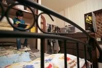 夜、自室でゲームをしながら母親の帰りを待つ子ども。2階建て一軒家のマナハウスは1階のリビングやキッチン、風呂やトイレが共有。6部屋が各母子世帯の居住スペースになっている=東京都世田谷区で2018年10月、和田大典撮影