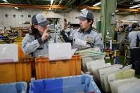 搬送機器メーカーの工場。何気ない風景だが、従業員たちは手話を交えて会話をしていた。聴覚障害者の深沢遼さん(中央)の入社後、お互いの誤解を防ぐため、約7年前から多くの同僚が数字などの手話を学んでいる。深沢さんは、コミュニケーションをしながら働く職場は「人と人がつながっている気持ちになれる」=山梨県昭和町で2018年11月7日、小川昌宏撮影