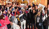 People celebrate in Osaka's Chuo Ward in the early hours of Nov. 24, 2018, after the city was selected to host the World Exposition in 2025. (Mainichi/Yoshiyuki Hirakawa)