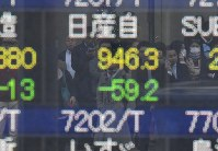 A monitor on the street shows the price of Nissan Motor Co. stock falling on Nov. 20, 2018, following the arrest of company chairman Carlos Ghosn. (Mainichi/Toshiki Miyama)