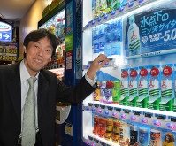 自動販売機の前で笑顔を見せる野村誠さん=東京都豊島区で、小野まなみ撮影