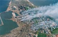 1993年7月12日、北海道南西沖を震源とするM7.8の地震。死者・行方不明者は230人。写真は海岸近くの住宅はすべて津波にさらわれた北海道奥尻島青苗地区=1993年7月13日、本社機から多河寛撮影